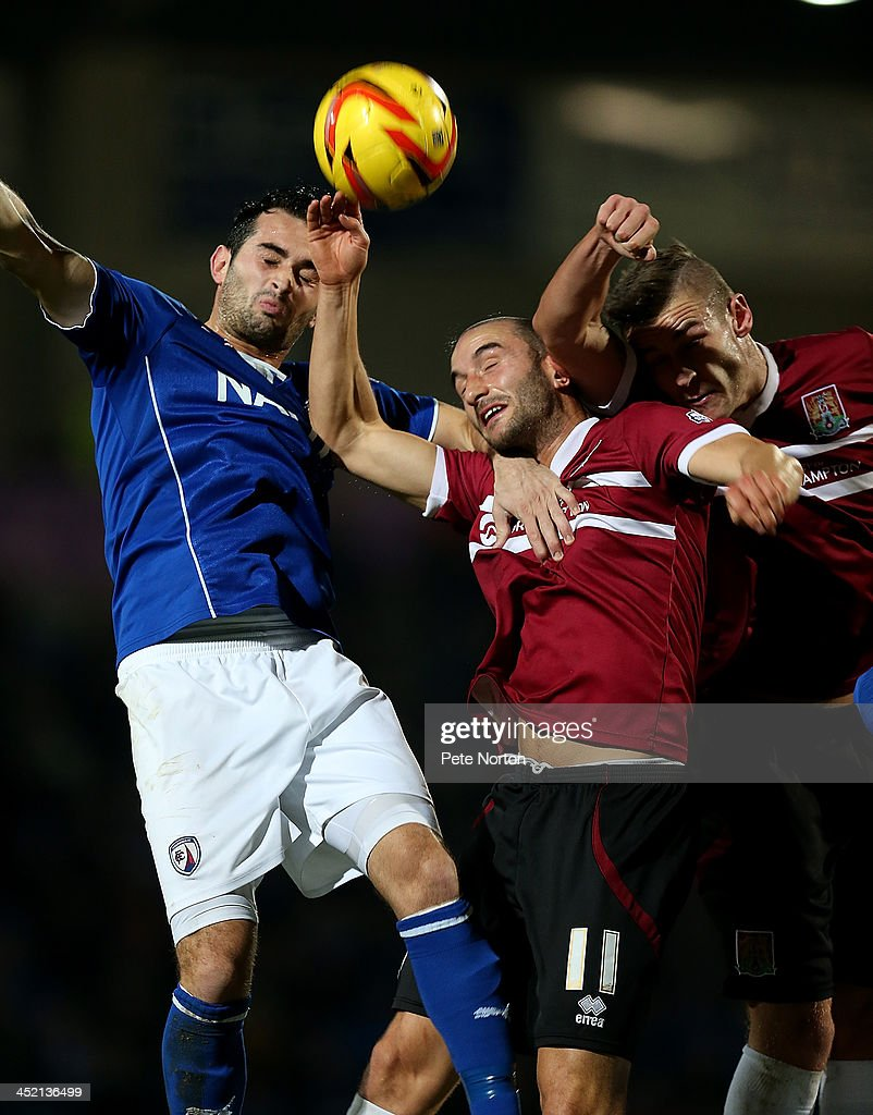 Sam Hird of Chesterfield contests the ball with Chris Hackett and Jacob Blyth of Northampton Town during the Sky Bet League Two match between Chesterfield and Northampton Town at Proact Stadium on November 26, 2013 in Chesterfield, England.