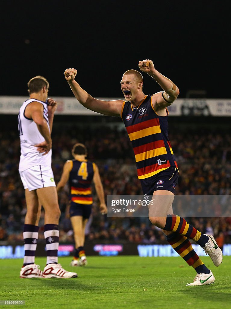 Sam Jacobs of the Crows celebrates on the final siren as <a gi-track='captionPersonalityLinkClicked' href=/galleries/search?phrase=Aaron+Sandilands&family=editorial&specificpeople=171132 ng-click='$event.stopPropagation()'>Aaron Sandilands</a> of the Dockers looks dejected during the AFL Second Semi Final match between the Adelaide Crows and the Fremantle Dockers at AAMI Stadium on September 14, 2012 in Adelaide, Australia.