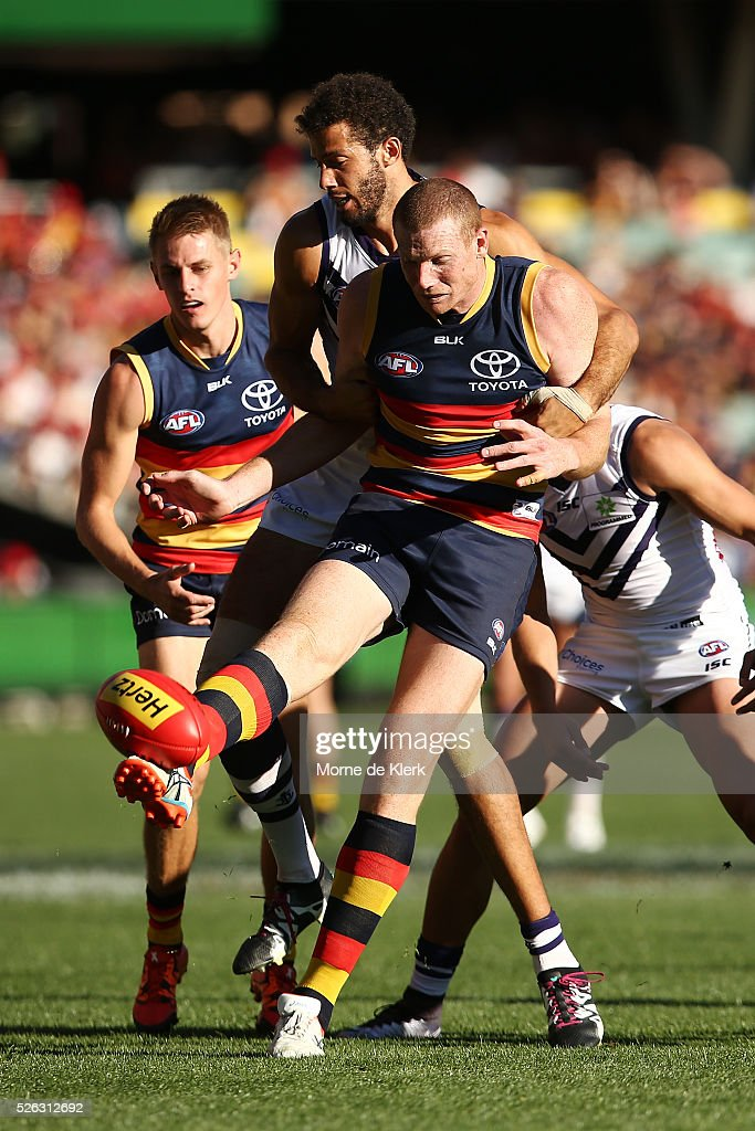 Sam Jacobs of the Crows gets a kick away under pressure from Zac Clarke of the Dockers during the round six AFL match between the Adelaide Crows and the Fremantle Dockers at Adelaide Oval on April 30, 2016 in Adelaide, Australia.