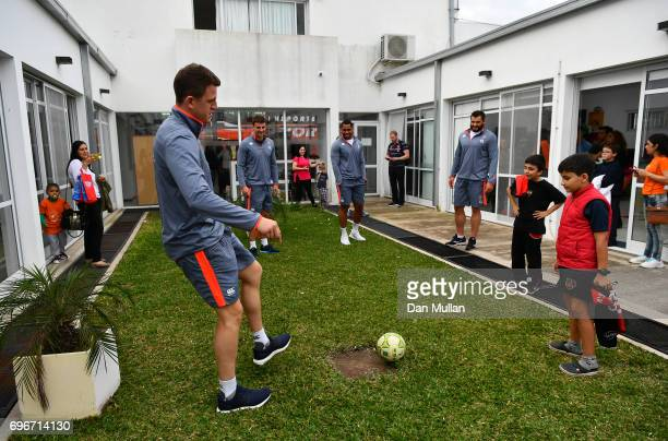 Sam James Ollie Devoto Joe Cokanasiga and Don Armand of England play football with patients during a visit to Fundacion Mateo Esquivo a local...