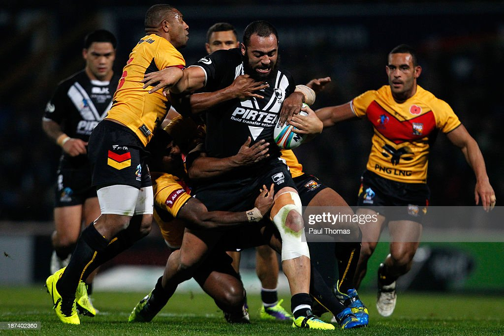 Sam Kasiano (C) of New Zealand is tackled by Jason Tali, Wellington Albert and Mark Mexico of Papua New Guinea during the Rugby League World Cup Group B match between New Zealand and Papua New Guinea at Headingley Stadium on November 8, 2013 in Leeds, England.
