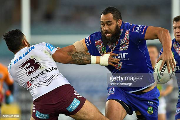 Sam Kasiano of the Bulldogs palms off Dylan Walker of Manly during the round 23 NRL match between the Canterbury Bulldogs and the Manly Sea Eagles at...