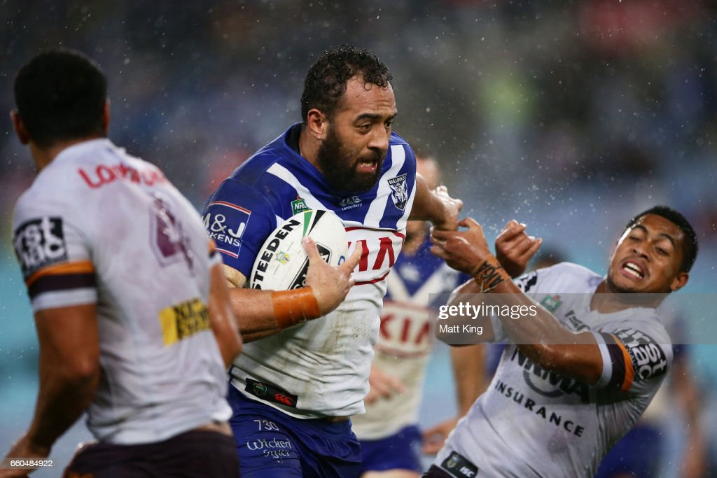 Sam Kasiano of the Bulldogs puts a fend on Anthony Milford of the Broncos during the round five NRL match between the Canterbury Bulldogs and the Brisbane Broncos at ANZ Stadium on March 30, 2017 in Sydney, Australia.