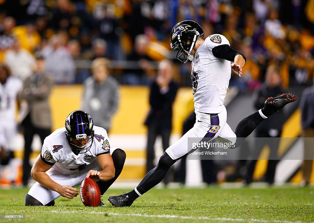 Sam Koch of the Baltimore Ravens holds the ball for kicker Justin Tucker as he attempts a 52yard field goal in overtime Tucker's kick led the Ravens...
