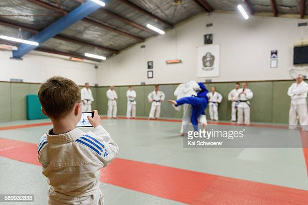 Sam Koster takes a photo while his father New Zealand Judo athlete Jason Koster fights during a training session at Can Am Ju on August 15 2016 in...