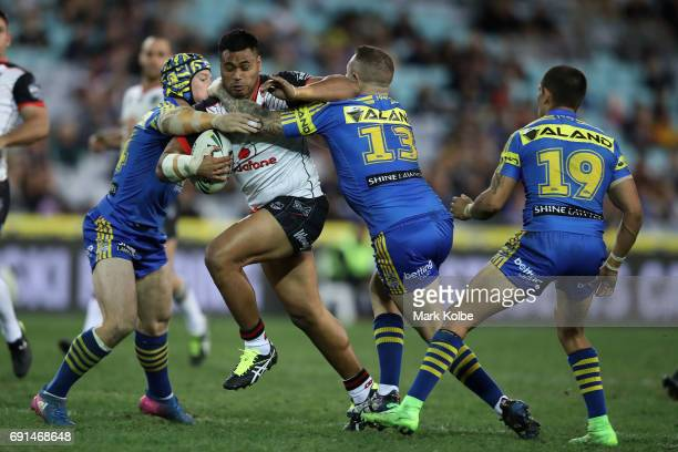 Sam Lisone of the Warriors is tackled by Beau Scott and Nathan Brown of the Eels during the round 13 NRL match between the Parramatta Eels and the...