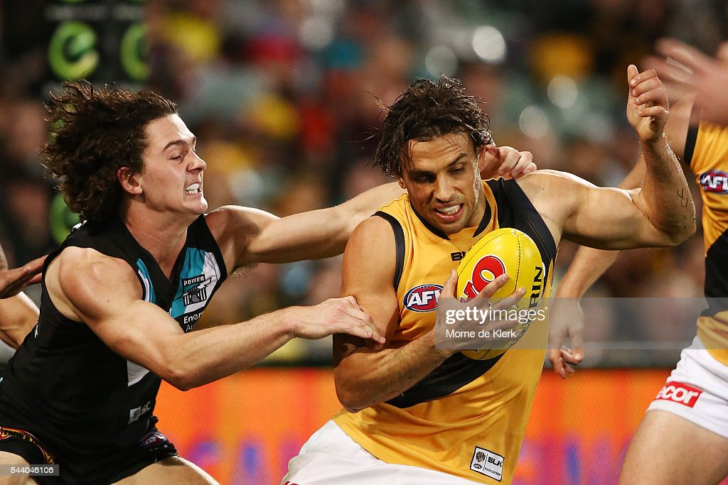 Sam Lloyd of the Tigers is tackled by Darcy Byrne-Jones of the Power during the round 15 AFL match between the Port Adelaide Power and the Richmond Tigers at Adelaide Oval on July 1, 2016 in Adelaide, Australia.