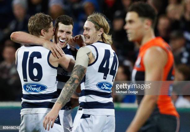 Sam Menegola of the Cats celebrates a goal with Scott Selwood and Tom Stewart during the round 23 AFL match between the Geelong Cats and the Greater...