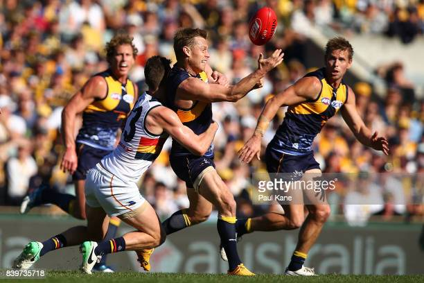 Sam MItchell of the Eagles gets his handball away while being tackled during the round 23 AFL match between the West Coast Eagles and the Adelaide...