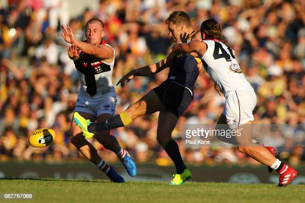 Sam Mitchell of the Eagles gets his kick away against Sebastian Ross and Maverick Weller of the Saints during the round two AFL match between the...