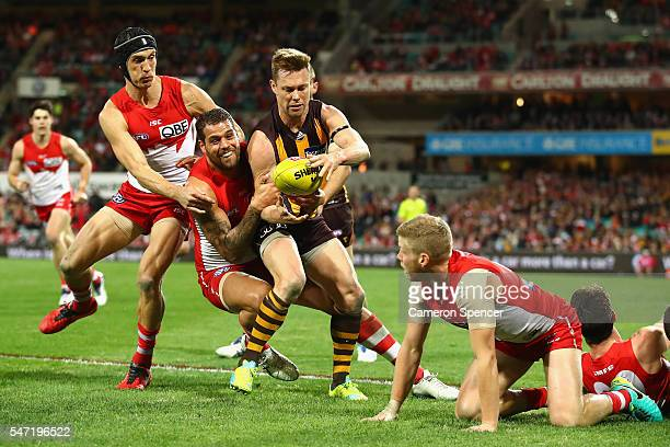 Sam Mitchell of the Hawks is tackled by Lance Franklin of the Swans during the round 17 AFL match between the Sydney Swans and the Hawthorn Hawks at...