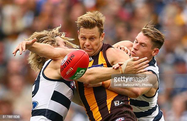 Sam Mitchell of the Hawks is tackled during the round one AFL match between the Geelong Cats and the Hawthorn Hawks at the Melbourne Cricket Ground...
