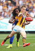 Sam Mitchell of the Hawks kicks whilst being tackled Nic Naitanui of the Eagles during the 2015 AFL Grand Final match between the Hawthorn Hawks and...