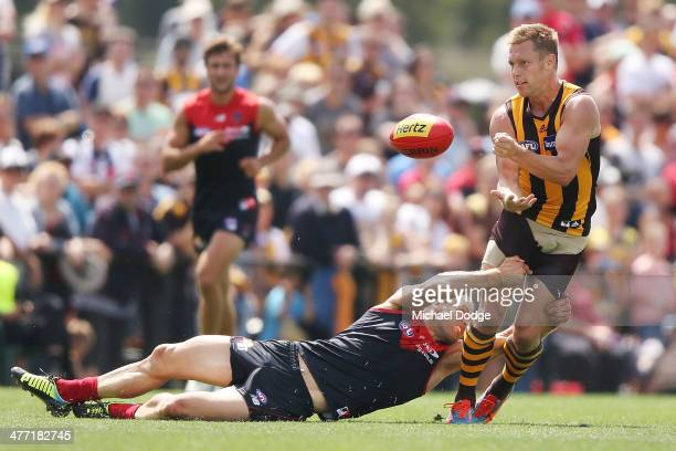 Sam Mitchell of the Hawks looks is tackled by Daniel Cross of the Demons during the AFL practice match between the Melbourne Demons and the Hawthorn...