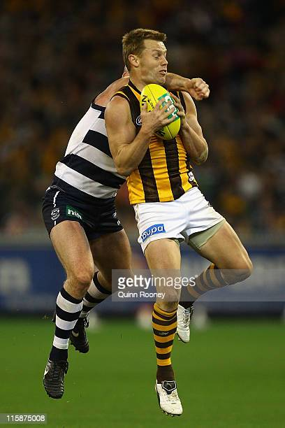 Sam Mitchell of the Hawks marks infront of Paul Chapman of the Cats during the round 12 AFL match between the Geelong Cats and the Hawthorn Hawks at...