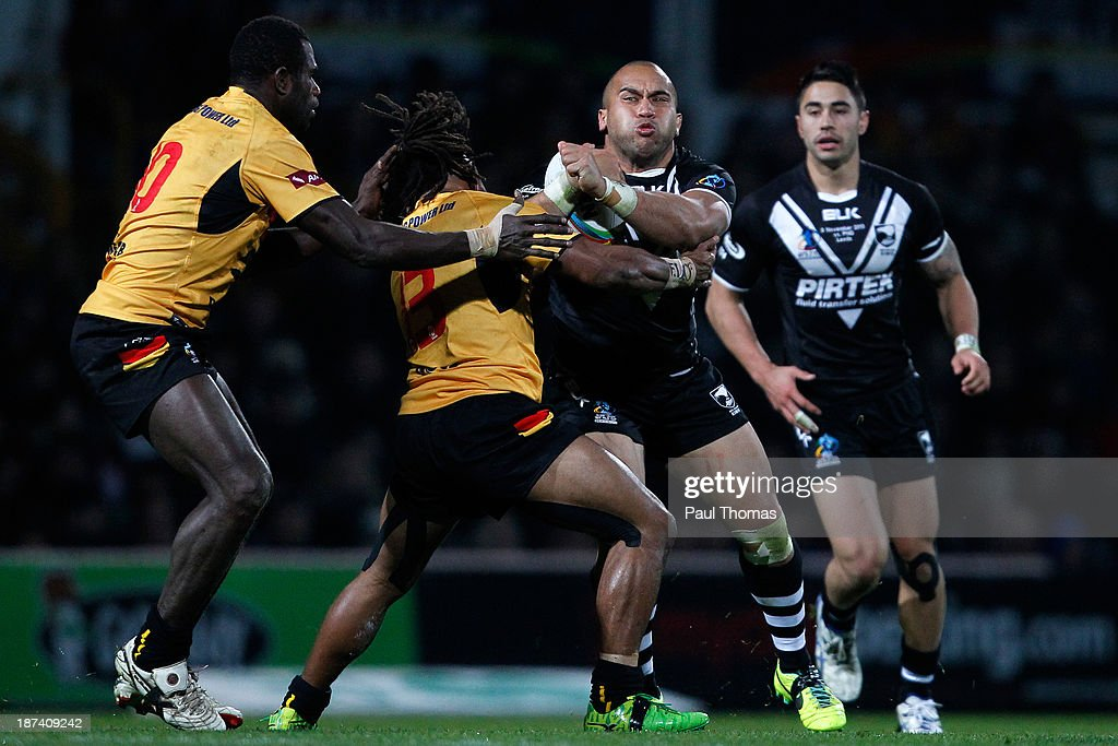 Sam Moa (C) of New Zealand is tackled by Sebastien Pandia and Joe Bruno (L) of Papua New Guinea during the Rugby League World Cup Group B match at Headingley Stadium on November 8, 2013 in Leeds, England.