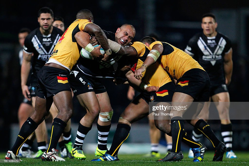 Sam Moa (C) of New Zealand is tackled by Wellington Albert, Mark Mexico and Jason Chan of Papua New Guinea during the Rugby League World Cup Group B match at Headingley Stadium on November 8, 2013 in Leeds, England.