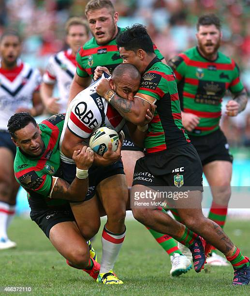 Sam Moa of the Roosters is tackled by Issac Luke and John Sutton of the Rabbitohs during the round two NRL match between South Sydney Rabbitohs and...