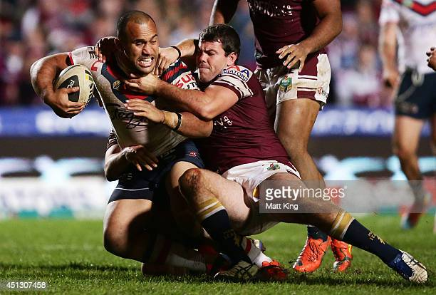 Sam Moa of the Roosters is tackled during the round 16 NRL match between the Manly Warringah Sea Eagles and the Sydney Roosters at Brookvale Oval on...