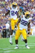Sam Montgomery and Tharold Simon of the LSU Tigers celebrate a tackle for loss during a game against the Washington Huskies at Tiger Stadium on...