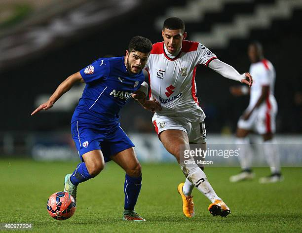 Sam Morsy of Chesterfield is tackled by Daniel Powell of MK Dons during the FA Cup Second Round Replay match between MK Dons and Chesterfield at...