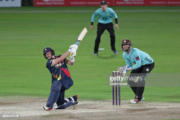 Sam Northeast of Kent Spitfires hits as as Surrey wicket keeper Ben Foakes looks on during the NatWest T20 Blast South Group match between Kent...