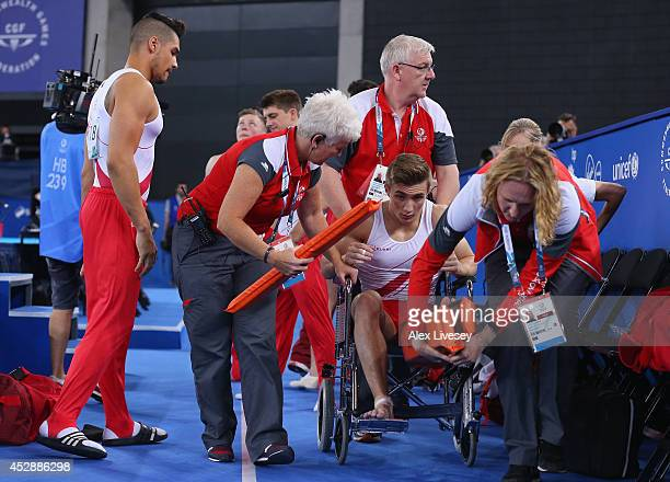 Sam Oldham of England is taken off the floor in a wheelchair after injuring himself during the Vault as team mate Louis Smith looks on at the...