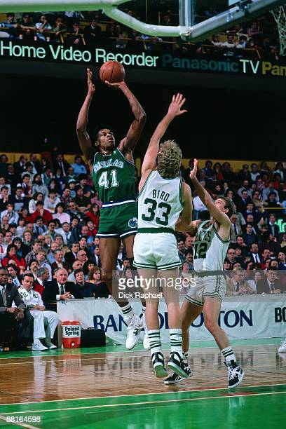 Sam Perkins of the Dallas Mavericks goes up for a shot against Larry Bird and Jerry Sichting of the Boston Celtics during an NBA game played in 1987...