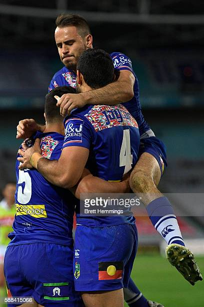 Sam Perrett of the Bulldogs celebrates with Curtis Rona and Josh Reynolds after scoring a try during the round 23 NRL match between the Canterbury...
