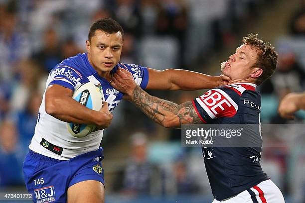 Sam Perrett of the Bulldogs fends off Jake Friend of the Roosters during the round 10 NRL match between the Canterbury Bulldogs and the Sydney...