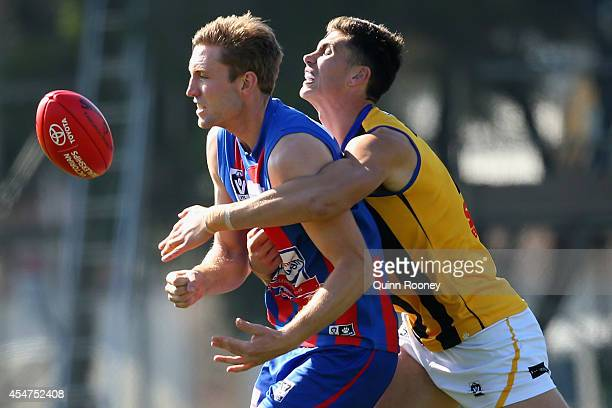 Sam Pleming of Port Melbourne handballs whilst being tackled by Lewis Pierce of Sandringhamduring the VFL Semi Final match between Port Melbourne and...