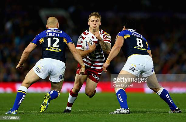 Sam Powell of the Wigan Warriors attempts to move past Carl Ablett and Kylie Leuluai of the Leeds Rhinos during the First Utility Super League Grand...