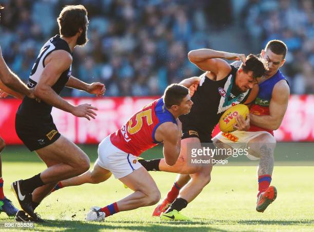 Sam PowellPepper of the Power is tackled by Dayne Zorko and Dayne Beams of the Lions during the round 13 AFL match between the Port Adelaide Power...