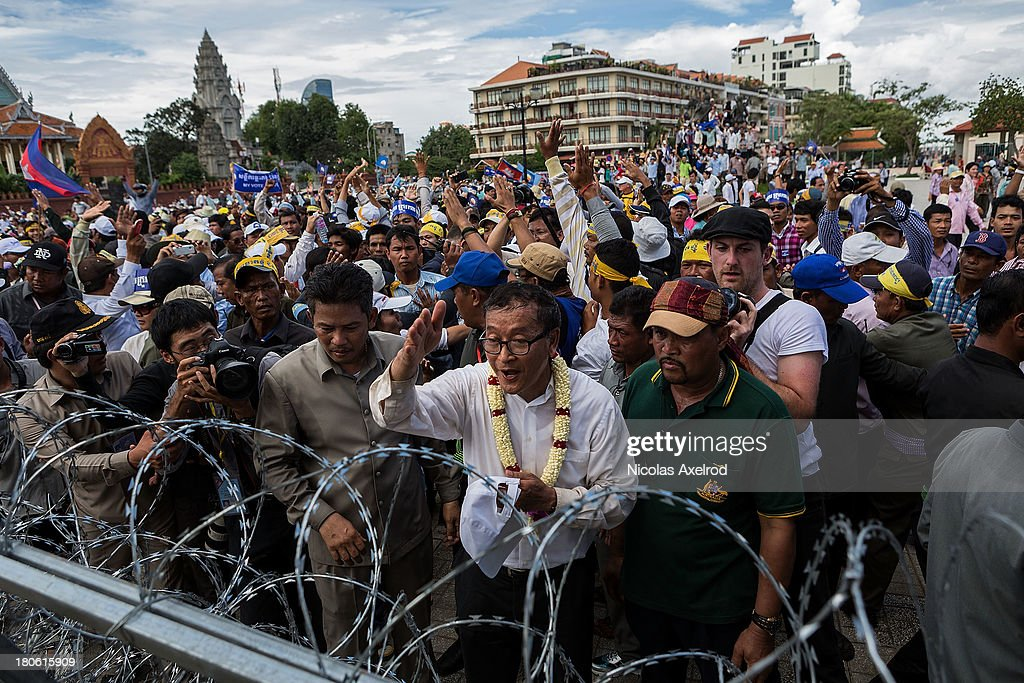 Sam Rainsy president of the Cambodia National Rescue Party addresses riot police in front of a barricade as he and supporters marched to the Royal...