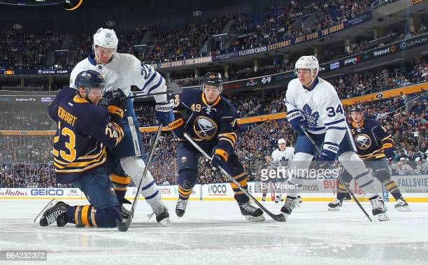 Sam Reinhart and CJ Smith of the Buffalo Sabres battle against Nikita Zaitsev and Auston Matthews of the Toronto Maple Leafs during an NHL game at...