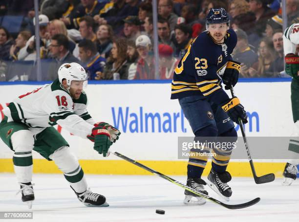 Sam Reinhart of the Buffalo Sabres passes the puck past Jason Zucker of the Minnesota Wild during the first period at the KeyBank Center on November...