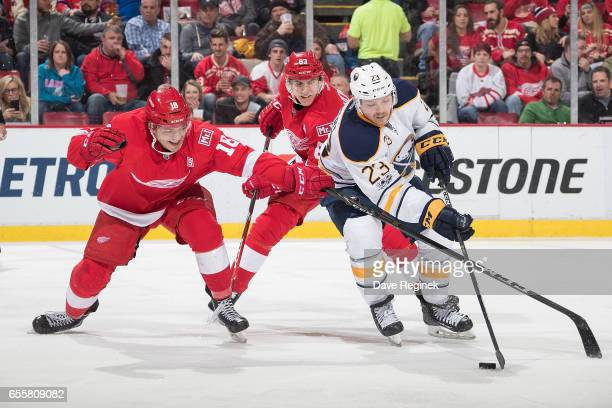 Sam Reinhart of the Buffalo Sabres skates with the puck while battling Robbie Russo and Tomas Nosek of the Detroit Red Wings during an NHL game at...