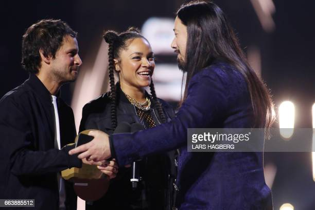 Sam Roberts and Tasha the Amazon present Rob Baker of the Tragically Hip the trophy for Group of the Year during the JUNO awards show at the Canadian...