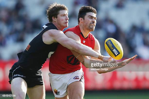 Sam Rowe of the Blues punches the ball away from Chris Dawes of the Demons during the round 21 AFL match between the Carlton Blues and the Melbourne...