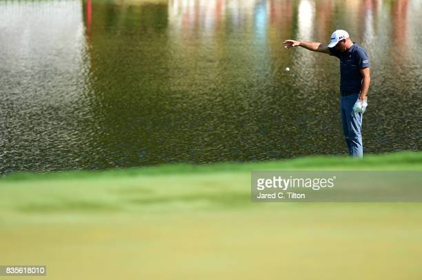 Sam Saunders plays a drop on the 15th hole after finding a water hazard during the third round of the Wyndham Championship at Sedgefield Country Club...