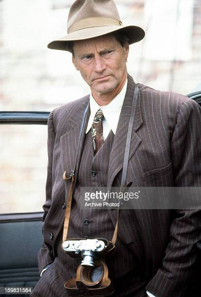 Sam Shepard with a camera hanging from his neck in a scene from the film 'Snow Falling On Cedars' 1999