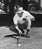 Sam Snead recent winner of the PGA tournament at Richmond Virginia sights a putt on the Medinah Country Club green where he will play in the National...