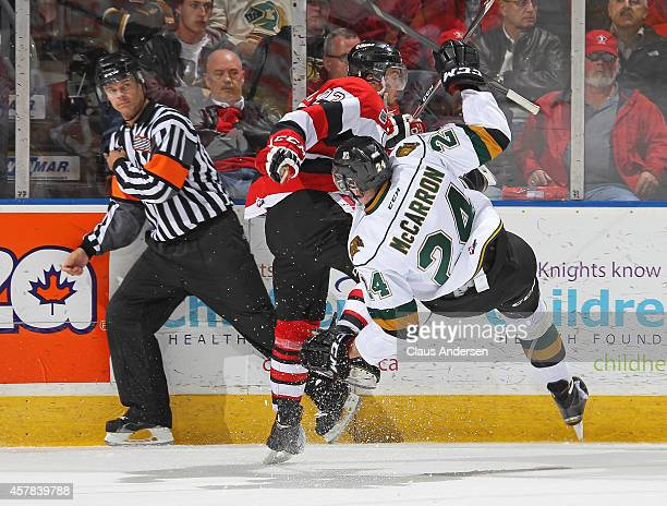 Sam Studnicka of the Ottawa 67's slams into Michael McCarron of the London Knights in an OHL game at the Budweiser Gardens on October 24 2014 in...