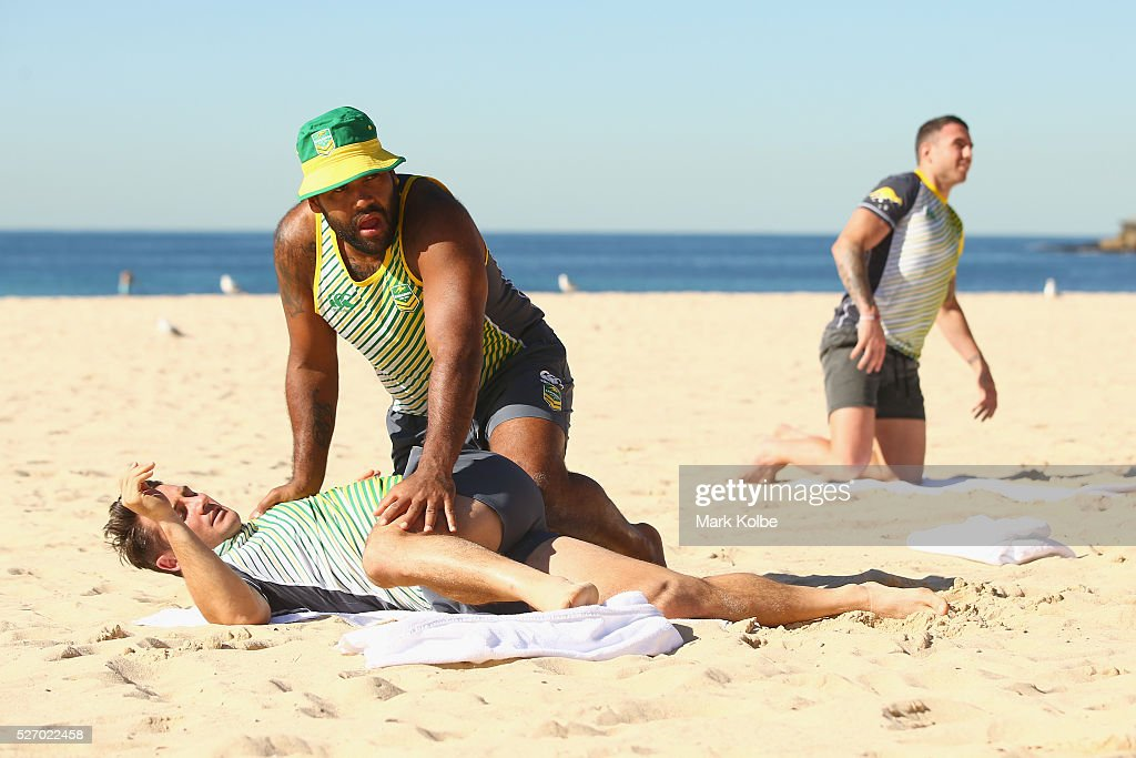Sam Thaiday assists Cooper Cronk during stretching at the Australia Kangaroos Test team recovery session at Coogee Beach on May 2, 2016 in Sydney, Australia.