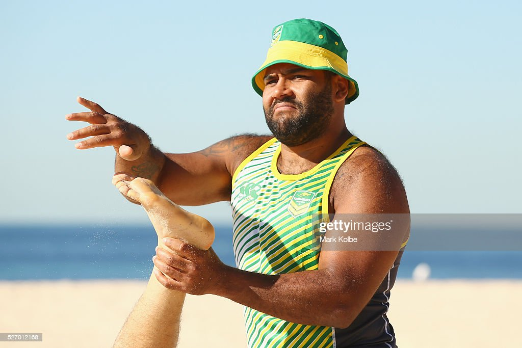 <a gi-track='captionPersonalityLinkClicked' href=/galleries/search?phrase=Sam+Thaiday&family=editorial&specificpeople=540245 ng-click='$event.stopPropagation()'>Sam Thaiday</a> brushes sand of the foot of Cooper Cronk during stretching at the Australia Kangaroos Test team recovery session at Coogee Beach on May 2, 2016 in Sydney, Australia.