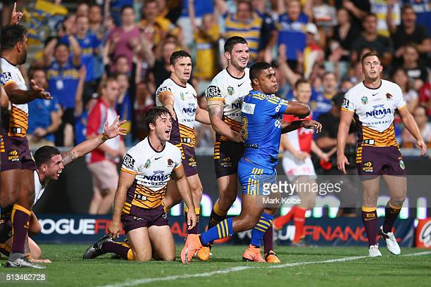 Sam Thaiday Darius Boyd Ben Hunt James Roberts and Matt Gillett of the Broncos look to the referee as Michael Jennings of the Eels celebrates scoring...