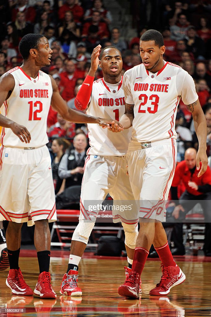 Sam Thompson #12 and Deshaun Thomas #1, both of the Ohio State Buckeyes, congratulate teammate Amir Williams #23 during a timeout against the Long Beach State 49ers on December 8, 2012 at Value City Arena in Columbus, Ohio. Ohio State defeated Long Beach State 89-55.