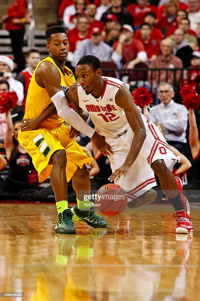 Sam Thompson #12 of the Ohio State Buckeyes drives against Carlin Dupree #13 of the North Dakota State Bison during the first half at Value City Arena on December 14, 2013 in Columbus, Ohio.