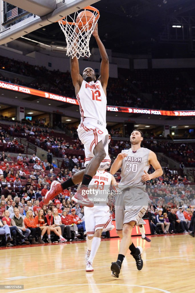 Sam Thompson of the Ohio State Buckeyes dunks in the first half as Hrvoje Vucic of the Walsh Cavaliers watches on November 3 2013 at Value City Arena...