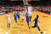 Sam Thompson of the Ohio State Buckeyes soars in for a slam dunk over Cedric Smith of the Savannah State Tigers in the second half on December 12...